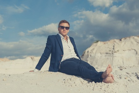 formalwear: Beautiful young man in formalwear sitting barefoot on sand in desert enjoying nature and the sun. Peaceful place to leisure. Stock Photo