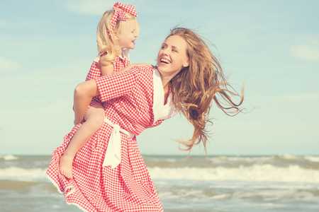 Happy family. Young beautiful  mother and her daughter  having fun on the beach. Positive human emotions, feelings. Retro toned