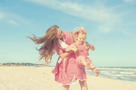 droll: Happy family. Young happy beautiful  mother and her daughter  having fun on the beach. Positive human emotions, feelings, emotions.