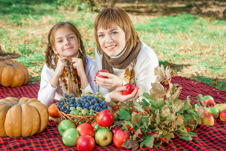 beautiful happy mother and daughter lying on a picnic. Autumn harvest. Apples, pumpkins, grapes, viburnum. Stock Photo