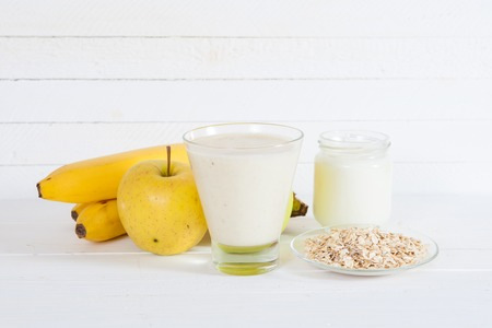 Smoothie with apple,banana, yogurt and oatmealon a light background. Ingredients.
