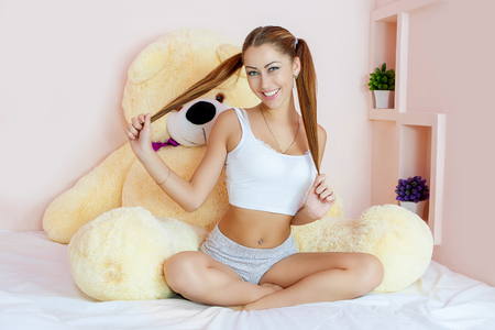 Young Beautiful  girl at bed.   Cheerful, happy, sexy woman enjoying a relaxing stay in her bed with a big toy bear. Stock Photo