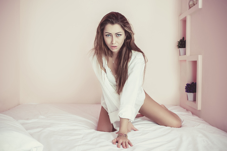coquettish: Young Beautiful  girl at bed.  Seductive sexy woman enjoying a relaxing stay in her bed.