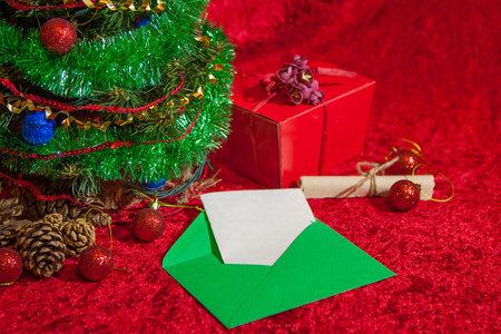 envelope decoration: Christmas Holiday Background, Hanging red baubles on Christmas tree, New Year backdrop, Decoration. Christmas Tree decorated. red open envelope with paper, greeting card