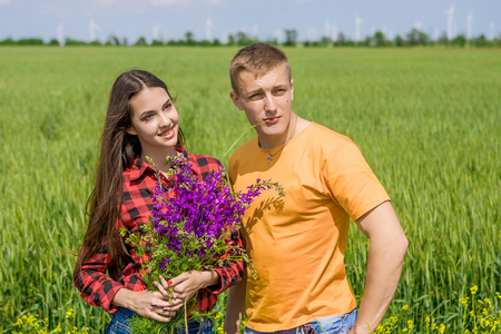 Beautiful girl and guy on field of wheat with bouquet of wildflowers Imagens