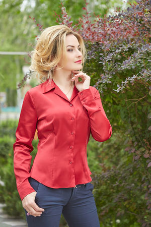 Beautiful Fashion girl in the garden in a red blouse. Beauty model woman face. Perfect Skin. Professional Make-up and hairstyle.Makeup.