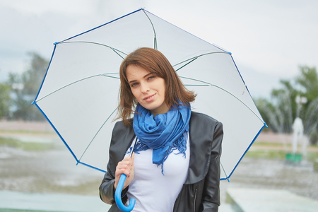 Beautiful young Fashion woman outdoors With umbrella near the fountain. Stock Photo
