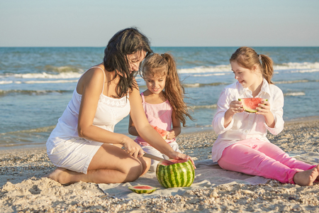 Happy family. Loving mother and two daughter on the beach with watermelon. One daughter with a disability with Down syndrome. Positive human emotions, feelings.