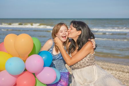Happy family. Loving mother with seventeen-year-old daughter with Down syndrome on the beach With balloons. Positive human emotions, feelings.