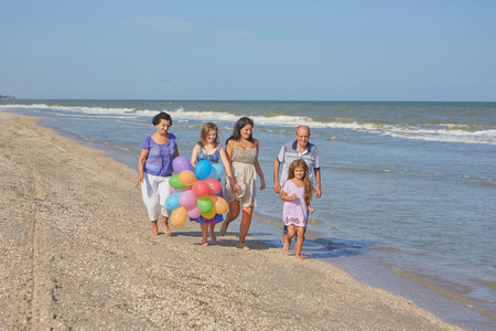 Happy family. Grandmother, grandfather, Loving mother and youngest daughter and an seventeen-year-old daughter with Down syndrome on the beach With balloons.  Positive human emotions, feelings.
