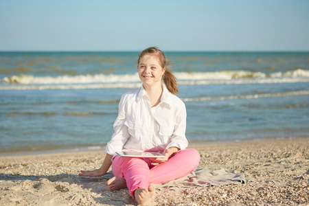 Cute Girl seventeen-year-old with Down syndrome on the beach play with the tablet. Positive human emotions, joy.