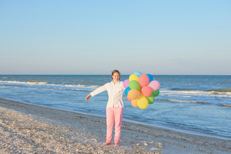 Happy Girl seventeen-year-old with Down syndrome on the beach with balloons. Positive human emotions, feelings.