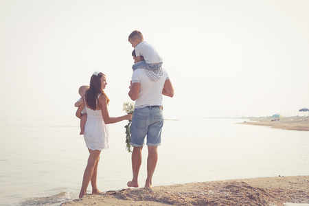 Happy family. Young  beautiful  parents and their two sons on the beach. Positive human emotions.