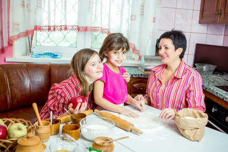 Mom teaching her two children cooking on the kitchen Archivio Fotografico