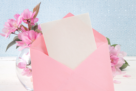 Ñard with an pink envelope and pink flowers of apple tree on wooden board. Place for inscription. Mothers day.