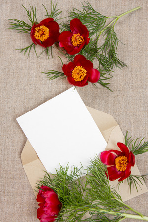 Ð¡ard with an envelope and red flowers on beige fabric. Place for inscription. Mothers day. Stock Photo