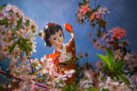 Statuette dancing geisha in the garden. Sakura with decorative lighting. Card in Japanese style. Stock Photo