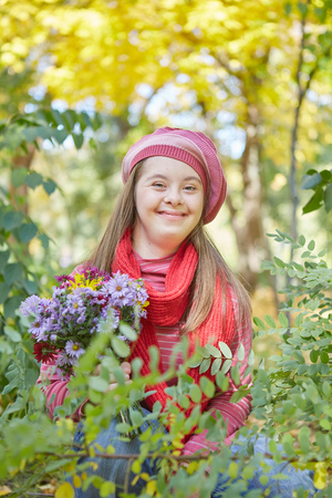 Girl with Down syndrome in autumn park. Happy and cheerful.