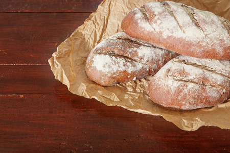 Bakery - gold rustic crusty loaves of bread on  dinner table background.