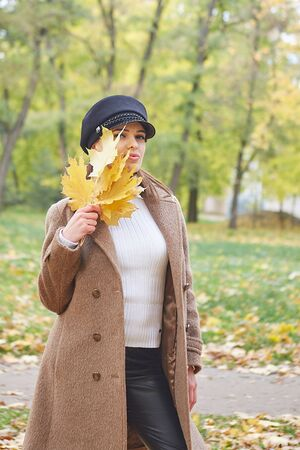 Beautiful gentle woman in the autumn park enjoys good weather and silence Stock Photo