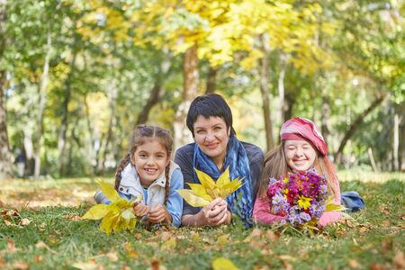 Happy family. Loving mother and two daughter in autumn park. One daughter with a disability with Down syndrome. Positive human emotions, feelings. Banque d'images