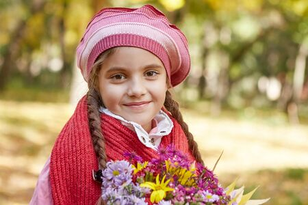 Beautiful happy girl in autumn park. The child dropped the first milk tooth.