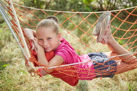Little girl lies in a wicker hammock, in the garden on a summer sunny day.