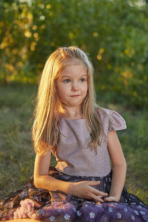 Little charming girl sitting on the grass in the summer garden, sunset.