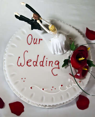 Wedding cake on a white backdrop with red rose petals Stock Photo