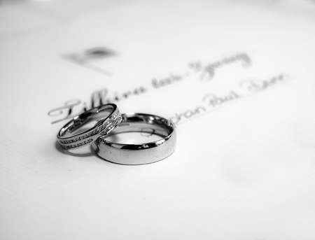 A pair of platinum wedding bands lying on Malta civil wedding certificate Stock Photo