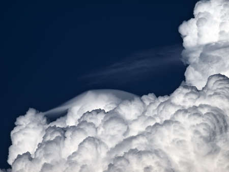 Towering detailed cumulus cloud with lenticular formations photo