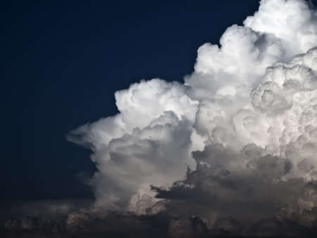 towering: Towering detailed cumulus cloud over a dark blue sky
