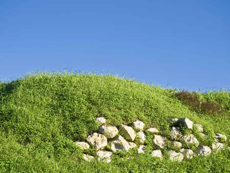med: Green grass in the Med and rubble wall Stock Photo