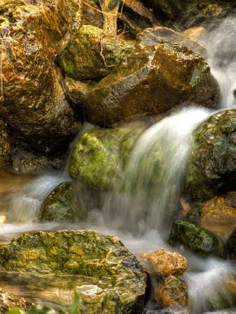 springwater: Flowing springwater seeping through rocks and stones