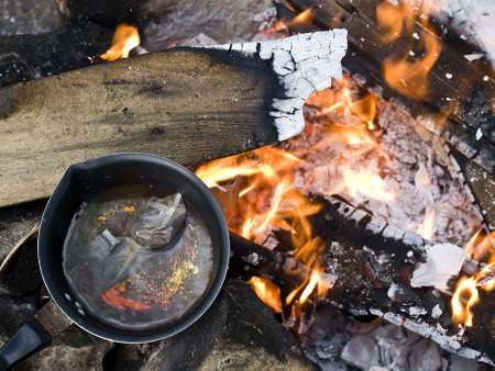 Making tea on a burning bonfire excellent to portray outdoor leisure activities such as camping Stock Photo