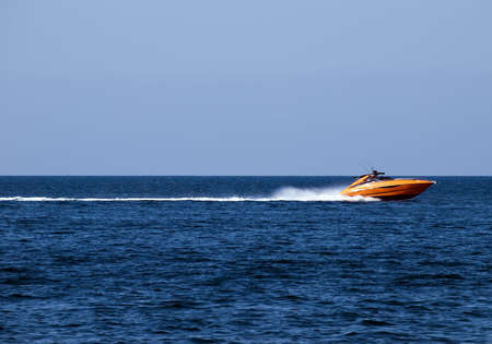 Orange speedboat speeding along the Mediterranean Sea off the coast in Malta