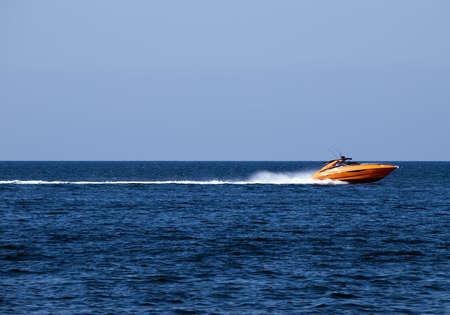 Orange speedboat speeding along the Mediterranean Sea off the coast in Malta