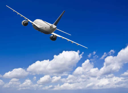 Civil aircraft travelling in deep blue skies with some cloud Stock Photo