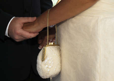 An intricately designed brides purse with couples hands in the background photo