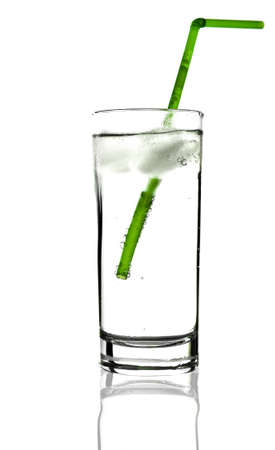 tumbler: Glass tumbler with green straw over white backdrop