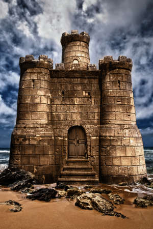 Beautiful sandcastle on a beach with turbulent skies in the background photo