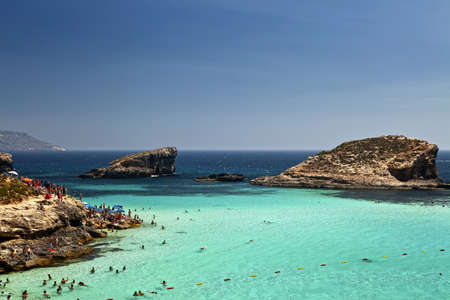 aboard: THE BLUE LAGOON, COMINO, MALTA - JUN 24 - The beautiful waters at The Blue Lagoon attract thousands of tourists aboard cruises during the summer months