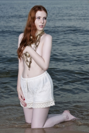 semi nude: A beautiful woman with pale skin and red hair kneeling on a beach posing semi nude Stock Photo