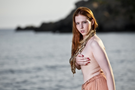seminude: Beautiful woman with pale skin and long red hair wearing Bohemian jewellery and posing semi-nude on a beach Stock Photo