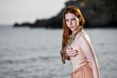 seminude: Bella donna con pelle chiara e capelli rossi lunghi che indossa gioielli boemi e posa semi-nuda su una spiaggia