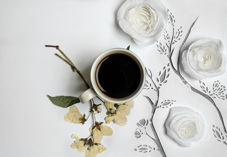 Coffee on a white background with pressed flowers and paper decor Reklamní fotografie