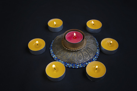 Circle of candles with candle in center Stock Photo