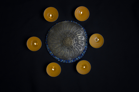 Circle of candles with pentagram in center Stock Photo