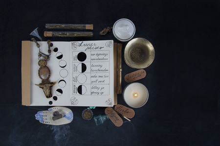 Wiccan Book of Shadows on black altar. Magical ingredients and incenses.