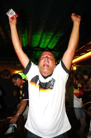 Een man het vieren van de overwinning van hun voetbalteam Redactioneel